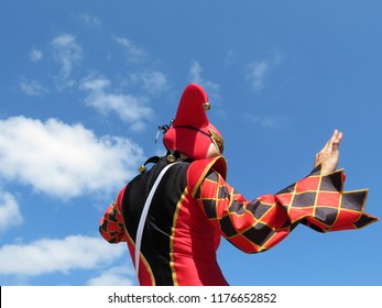 Person in a jester costume isolated on blue sky with white clouds, carnival concept. Harlequin in black-red foolscap with bells, girl dressed as a Joker