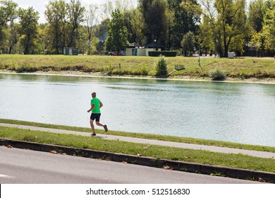 A person jogging along the river