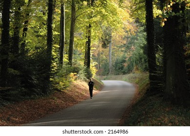 Person Jogging in the Woods in Autumn. Face not recognizable