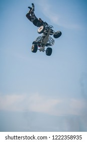 A person jumping with a quad bike high up in the sky and making a trick. Stuntman on a quadbike.