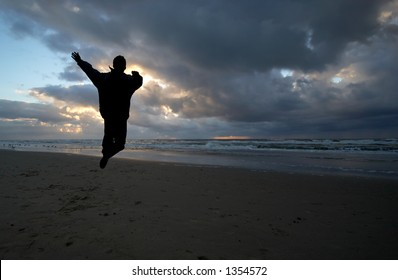 Person jumps in the air on a beautiful night on the beach