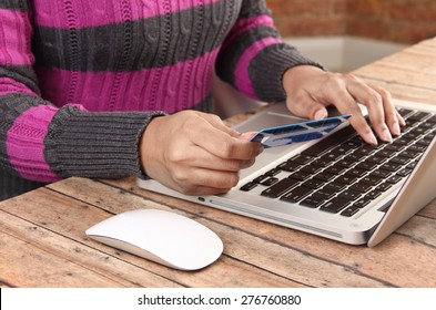 Person with laptop using a credit for online banking and shopping - concept for e-commerce and online banking