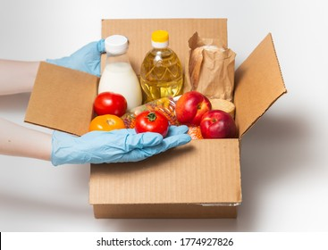 Person in latex gloves has holding a box with ordered goods.Safe food delivery service under quarantine. Online food shopping service or donation concept. White background.High quality close up photo