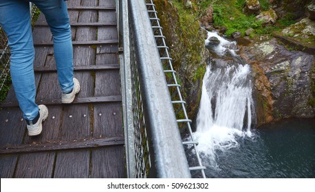 Person legs (woman) crossing a high bridge over a waterfall near the Jenolan Caves  at the Blue Mountains in New South Wales, Australia.