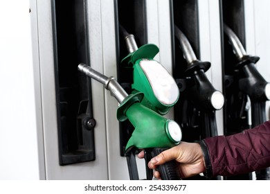 Person lifting Fuel pump at the petrol station to fill the vehicle