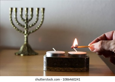 person lighting Sabbath candles on a table