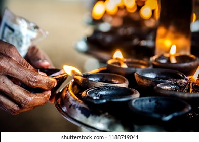 A person lights a candle in a Buddhist temple. Kalutara. Sri Lanka.
