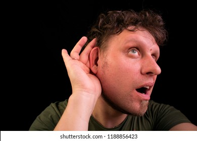 The person listens very attentively. He pushes his ear and listens. His face is surprised and delighted with what he has heard.
