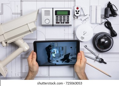 Person Looking At Office Security Camera On Mobile Phone With Security Equipments On Blueprint Document