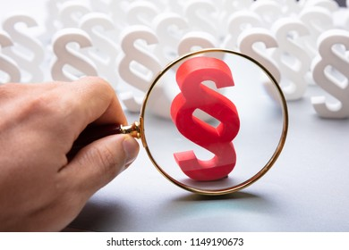 A Person Looking At Red Paragraph Symbol Through Magnifying Glass