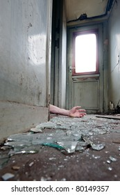 A person lying in doorway unconscious in messy environment.