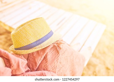 Person lying on a sunbed with a blanket and a beach hat. Straw hat on a hot day off.