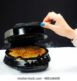 Person making fresh waffles with a waffle maker towards black on white
