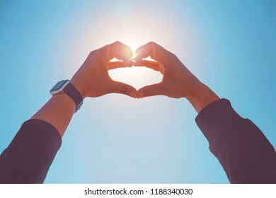 person making a heart shape with their hands against the sun in a blue sky toned with a retro vintage instagram filter