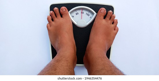 a person (man) is weighing himself on a scale. the scale shows the number 89 kilograms. these scales use units of kilograms.