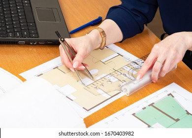 A person measures the size of the room according to the drawings. Architect with a ruler in his hands. Concept - approval of building drawings. Woman's hands with dividers and ruler.