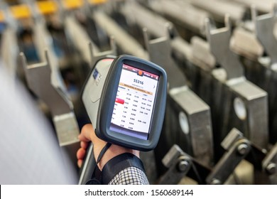 The person is measuring chemical values on the steel plate with a portable handheld x ray chemical analyser or spectrometer. Meaning of the writes on the screen is SS316 (ASTM A 316 steel material).