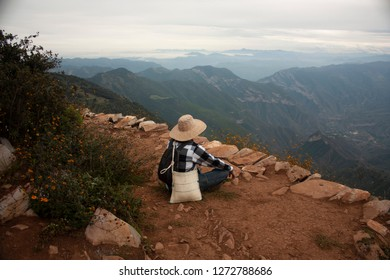 Person meditating in the chasm of the mountain four sticks in Mexico with a view to the Sierra Gorda