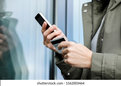 Person with mobile phone and credit card, Online shopping buying with mobile phone, wireless all over, payment cashless