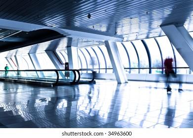 Person move in modern glass corridor in airport