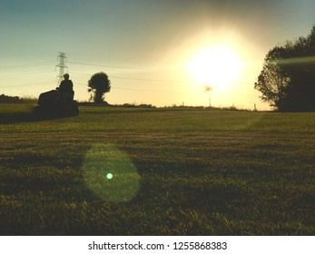 Person mowing the grass at sunset