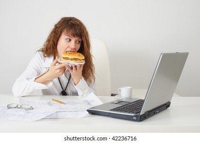 The person at office on a workplace eats a hamburger