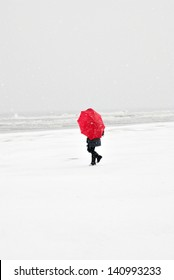 person on the beach with red umbrella in snow storm
