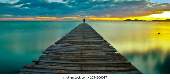 Person on the jetty at sunrise enjoying the tranquility and relax