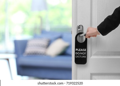 Person opening door with sign PLEASE DO NOT DISTURB on handle at hotel