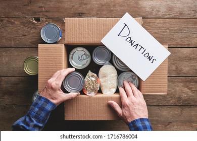 eine Person, die eine Spenderbox mit Lebensmitteln verpackt