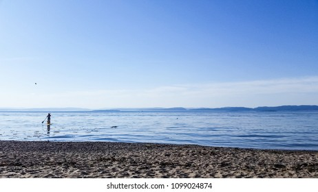 Person paddleboarding next to beach under beautiful blue sky at waterfront