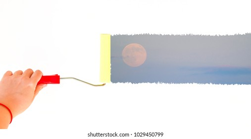 person painting the moon on a white wall with a roller brush