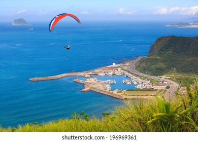 A person paragliding above the ocean on a sunny day.