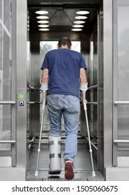 Person Patient mit Krücken und gebrochenem Bein in den Krankenhausaufzug