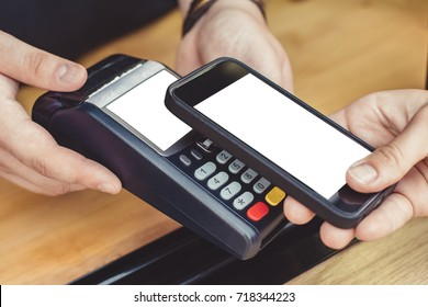 Person paying pay through smartphone using NFC technology in outdoor cafe.