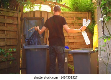 Person performing a selective sorting of household waste in recycling bins. Man putting plastic bottles in a yellow container and garbage in a bag in a green container.