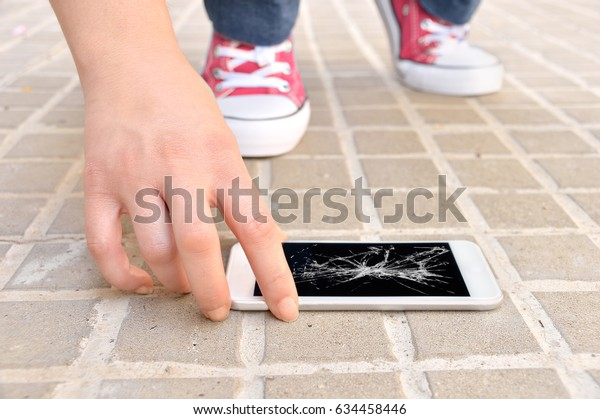 Person picking broken smart phone with cracked screen of the ground