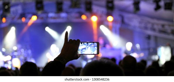 person with the pinky hand raised while photographing the rock concert using a modern smartphone