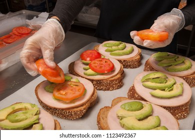 Person in plastic gloves laying out 6 turkey avocado and tomato sandwiches.
