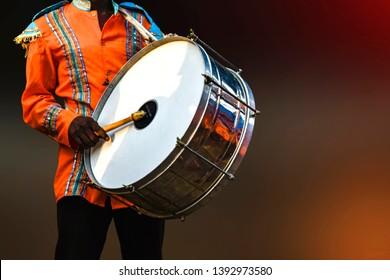 A person playing Drumhead,  - A drumhead or drum skin is a membrane stretched over one or both of the open ends of a drum. The drumhead is struck with sticks, mallets, or hands.