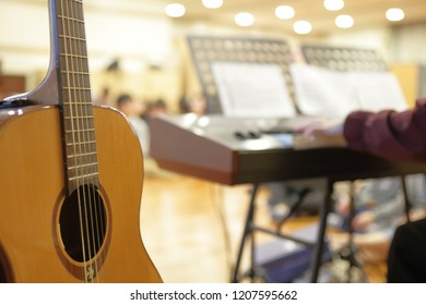 A person playing an electric piano A guitar set up behind