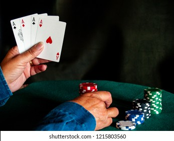 A person playing poker with the four aces of a deck in his hand and poker chips of various colors on a green mat