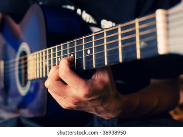 The person plays a guitar, fingers hold a chord