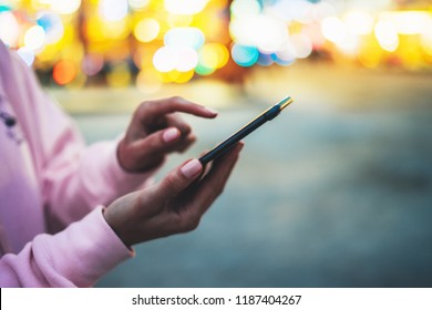 Person pointing finger on screen smartphone on defocus background bokeh light in evening street, hipster girl using in hands mobile phone gadget in night atmospheric city, online wifi internet concept