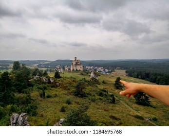 Person pointing finger on some abandoned castle ruins in the background. Nature outdoors recreation. People on the top of the mountain looking on the landscape.