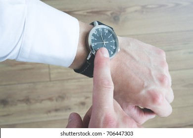 A person pointing at his watch on his wrist with his index finger. Look at the time.