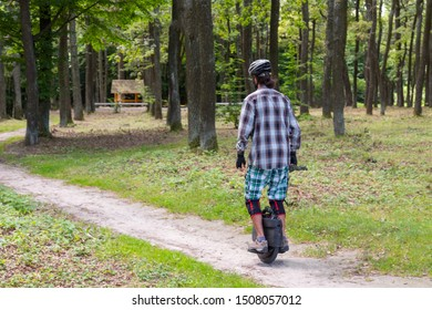 Person in protective wear rides a monowheel at the forest. Technology concept with copy space.