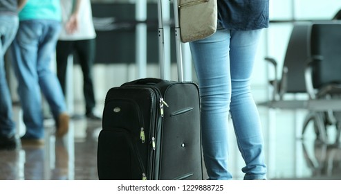 Person pulls suitcase at the airport. Woman carrying luggage