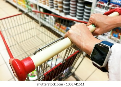Person pushing shopping trolley cart against modern supermarket aisle blurred background