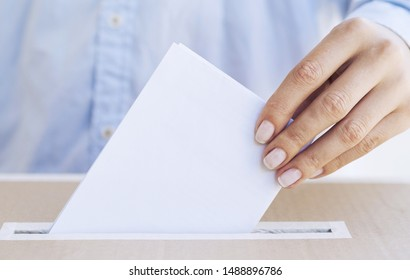 Person putting empty ballot in a box close-up